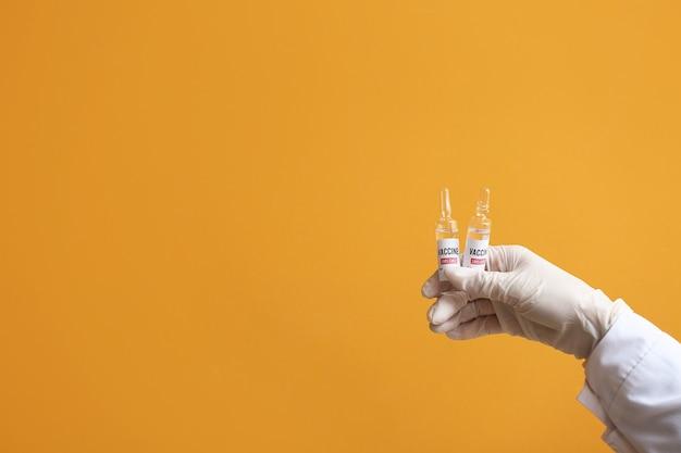 오렌지 배경에 covid-19에 대한 백신과 의사의 손