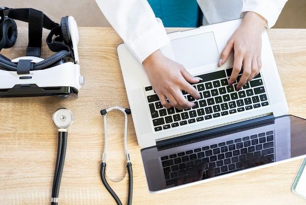 コンピューターを使用して机に向かって医師の手と翼のあるストートコープとビジョングラス