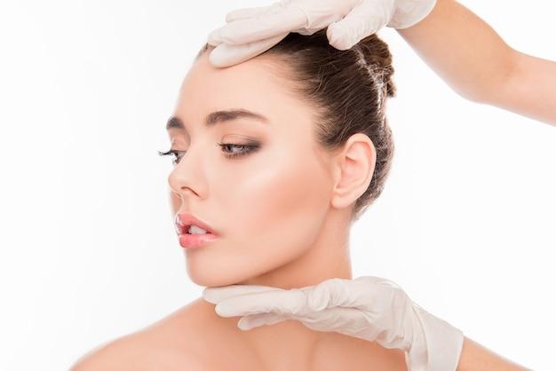 Руки врача проверяют кожу перед пластической операцией Premium Фотографии