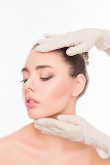 Руки врача проверяют кожу перед пластической операцией