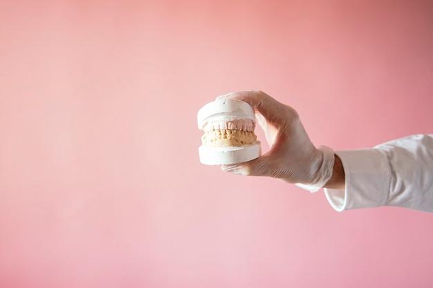 Руки врача, показывающие композитные зубные протезы на розовом фоне.