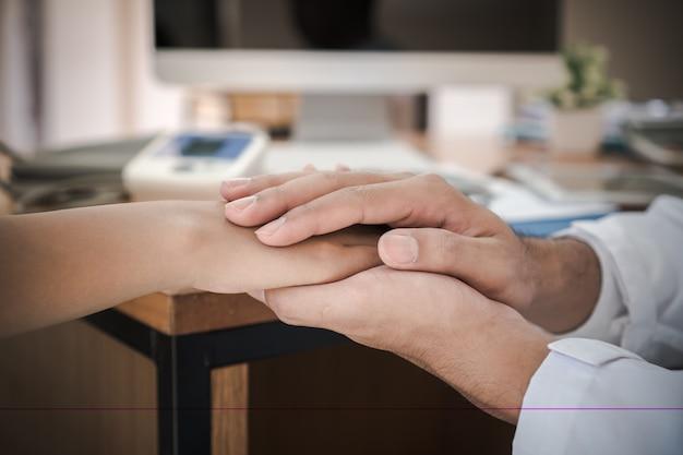 의사의 병원에서 진찰을 받은 후 희망의 지지를 위한 친절한 격려 공감과 신뢰 치료를 응원하는 나쁜 소식으로 안심시키기 위해 여성 환자의 손을 잡고 있는 의사의 손
