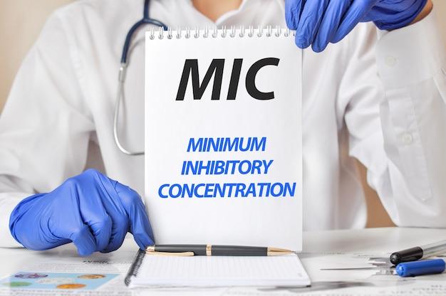 텍스트 mic와 종이 한 장을 들고 파란색 장갑에 의사의 손. mic-최소 억제 농도의 줄임말, 의료 개념.