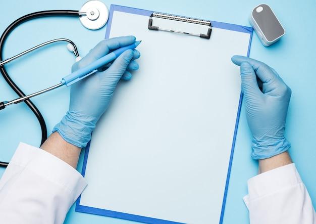 Руки врача в синих медицинских перчатках держат электронный пульсоксиметр на синем фоне, вид сверху