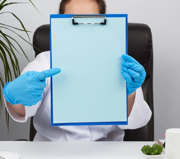 青い医療用ラテックス手袋で医師の手がペーパークリップのフォルダーを保持