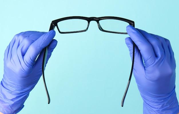 Руки врача в перчатках держат очки на синем