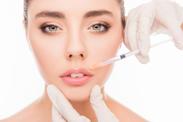 Руки врача делают укол в губы женщины