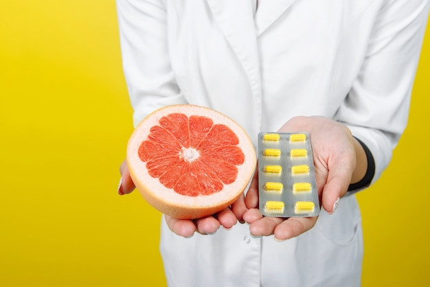 Руки врача, на которых таблетки и фрукты