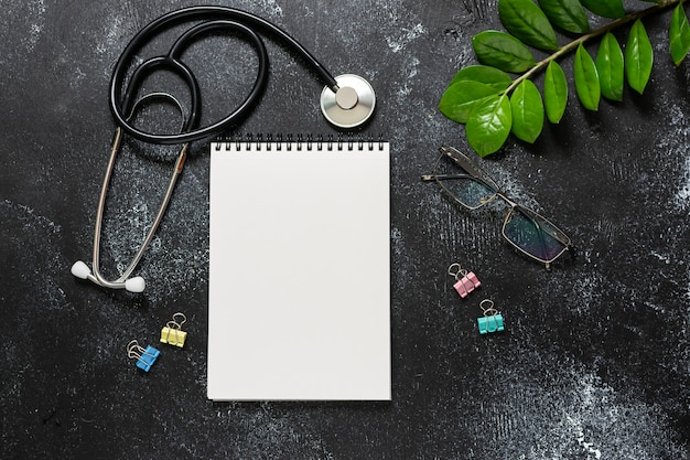 Doctor's office concept with blank notepad, medical stethoscope, glasses and green plant on black wooden table top view.