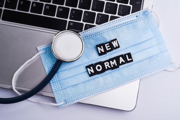 Кабинет врача с современным рабочим местом в медицинской клинике. ноутбук, стетоскоп и медицинская маска с надписью new normal на виде сверху.
