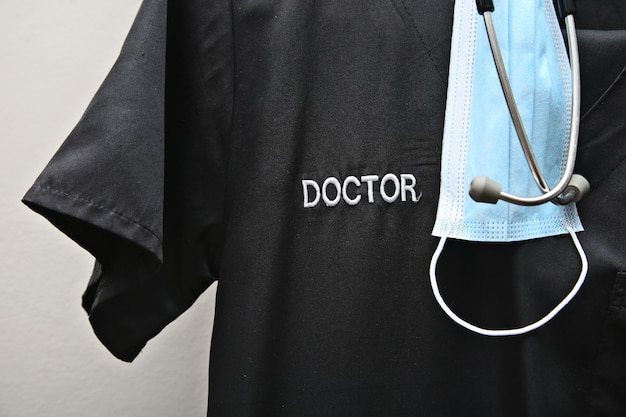 A doctor's scrubs, stethoscope and face mask.