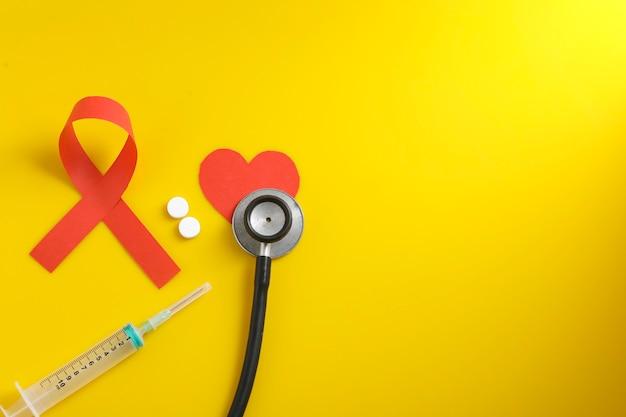 Рабочее место врача со стетоскопом, блистерными таблетками, шприцем на желтом фоне.