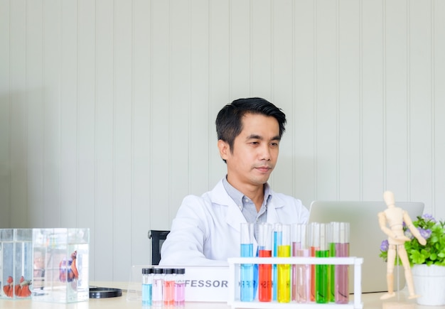 Доктор ученый мужской рабочий ноутбук с боевым аквариумом и цветной пробиркой