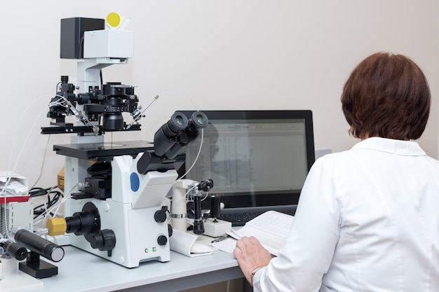 Doctor or scientist working with computer and microscope in biotech lab, equipment in laboratory of fertilization, ivf.