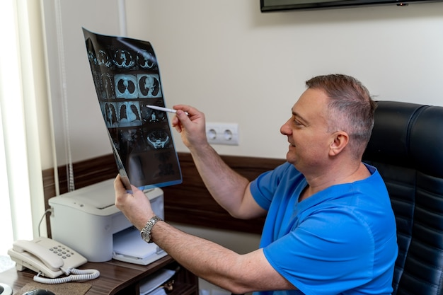 Doctor in scrubs sitting at office. x-ray in hands. medical results at doctor s hands.