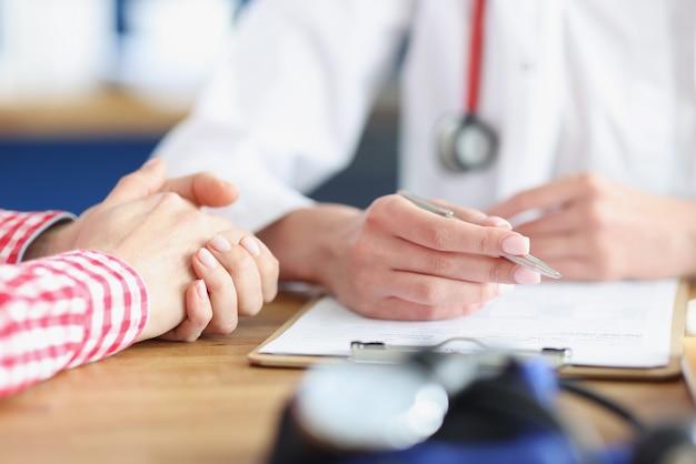 의사는 환자를보고 카드에 의료 지표를 기록합니다.
