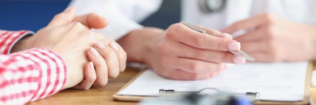 医師は患者を見て、カードに医療指標を書き留めます