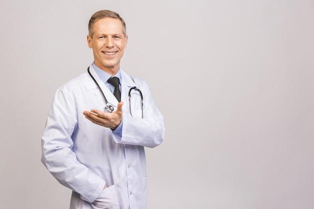 의사 수석 남자, 의료 전문가 회색 벽 위에 절연 빈 손으로 뭔가 들고.