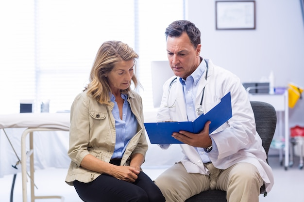 Doctor and senior woman discussing on file