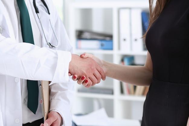 医者はオフィスのクローズアップで患者とこんにちはとして握手をします