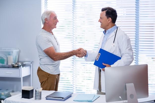 年配の男性人と握手する医師