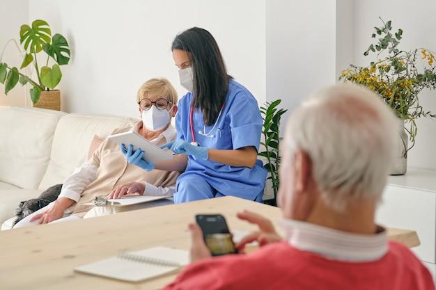 自宅で男性に対して高齢患者とタブレットを共有する医師