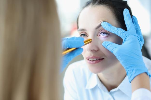 医者は患者の目のクローズアップにレーザーを照らします