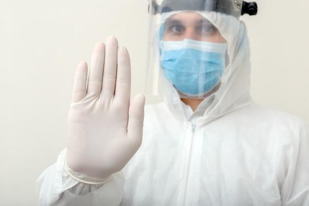 Знак выставки доктора остановите жест нет к пандемическому защитному костюму covid-19, coronavirus нося и лицевой маске на белой предпосылке.