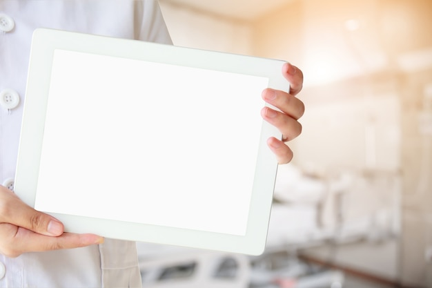Doctor show tablet computer with abstract hospital room interior with bed blur background