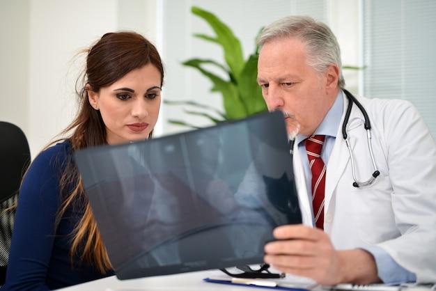 Врач показывает рентгенограмму колена для пациента