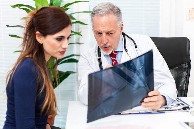 Врач показывает рентгенограмму пациенту