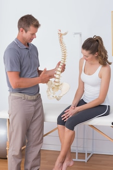 Врач показывает анатомический позвонок своему пациенту