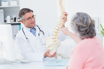 Doctor showing anatomical spine while patient touching it