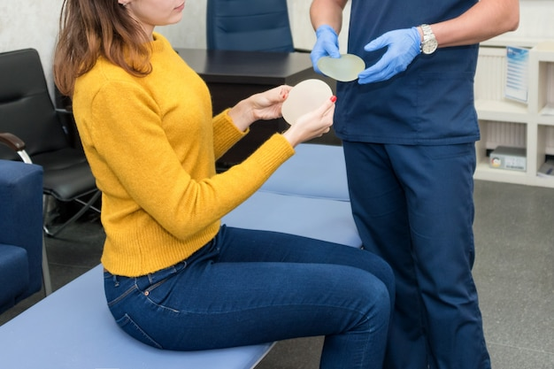 Doctor showing breasts implants to female patient
