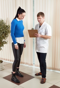 Доктор показывая пациентке ее результаты медицинского теста в коридоре