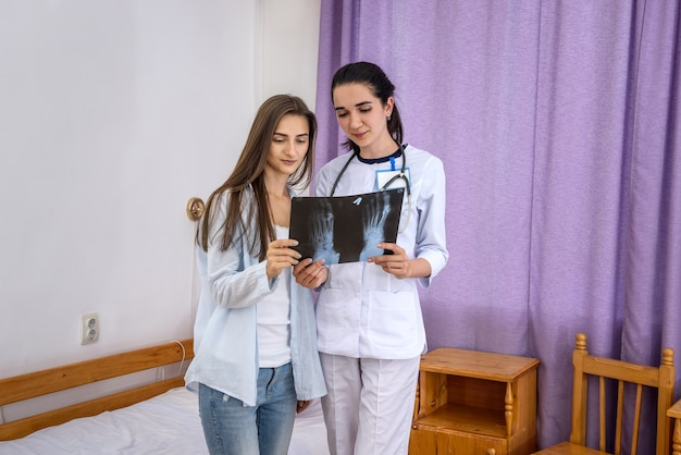 환자에게 발 엑스레이를 보여주는 의사. 두 사람은 병원에서 그것을 보고 있다.