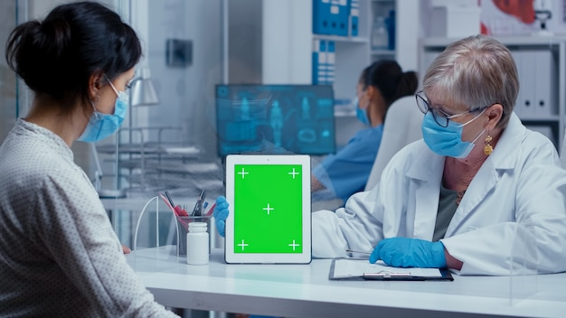 의사는 마스크와 보호 장갑을 끼고 플렉시글라스 벽을 통해 환자에게 녹색 화면 태블릿을 보여줍니다. sars-cov-2 글로벌 건강 판의 보호 장비 개념 샷에서 의료 상담