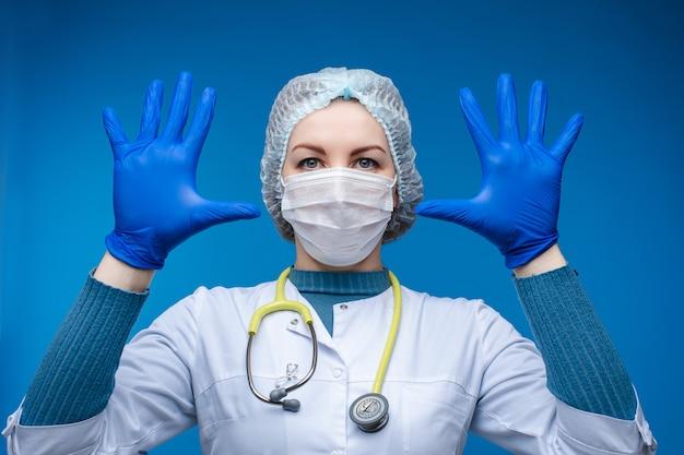 青い保護手袋で彼女の手を示す医師。