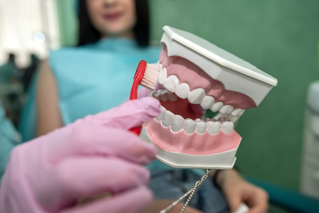 Doctor showing how to clean teeth rightly to a patient