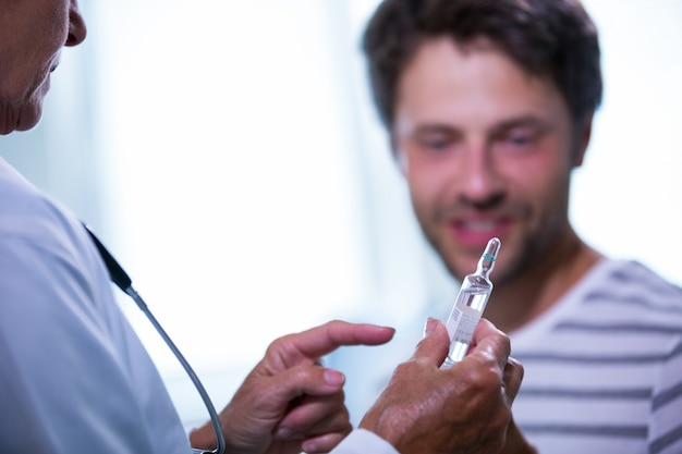 Doctor showing injection to patient