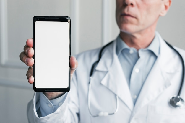 Medico che mostra un telefono cellulare
