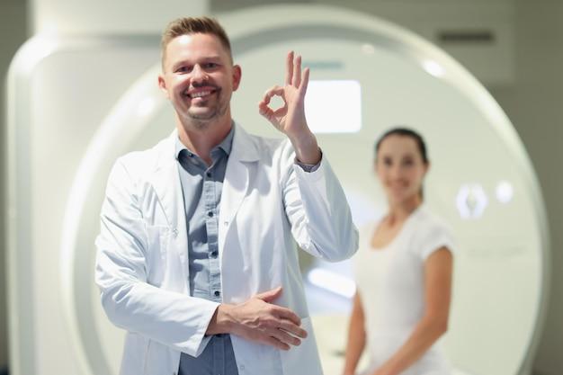 Mri 기계 highquality에서 여성 환자의 배경에 대해 확인 제스처를 보여주는 의사