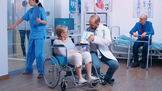 Doctor showing the osteoporosis risk for elderly persons to a senior woman in wheelchair in a rehabilitation clinic, center or hospital. old man with walking frame, health care medical facility, moder