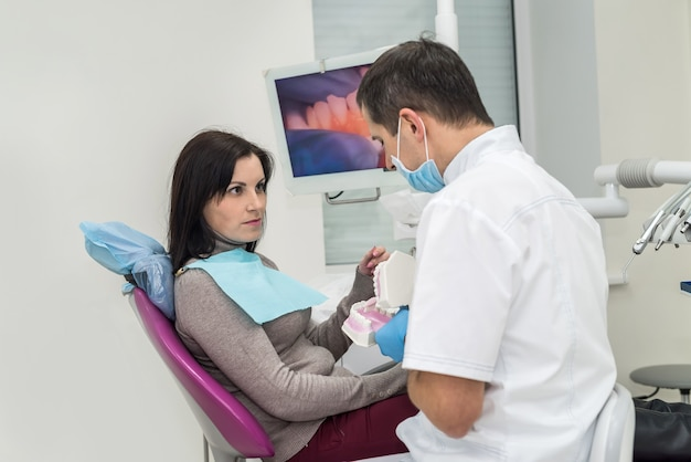 Doctor showing patient how clean teeth on jaw sample