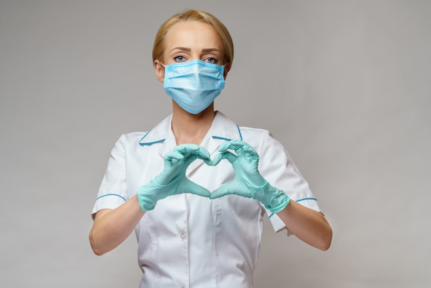 Doctor showing shape of heart by his hands in sterile gloves