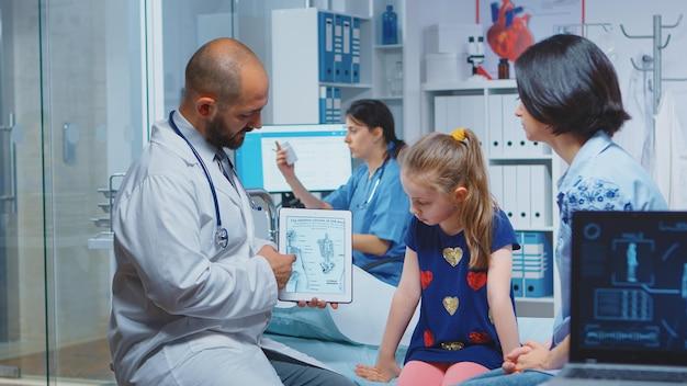 診察中にタブレットにスケルトングラフィックを表示する医師。病院で医療サービスのx線治療検査を提供する医学の医療従事者医師の専門家