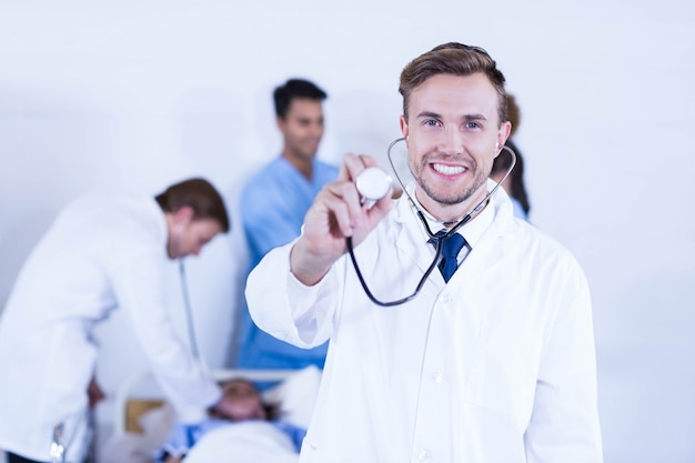 Doctor showing stethoscope towards camera and other doctor examining a patient behind in hospital