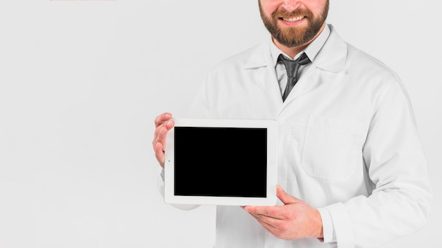 Doctor showing tablet and smiling