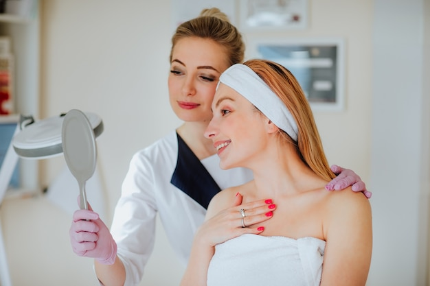 キャビネットに小さな鏡を持っている患者に結果を示す医師