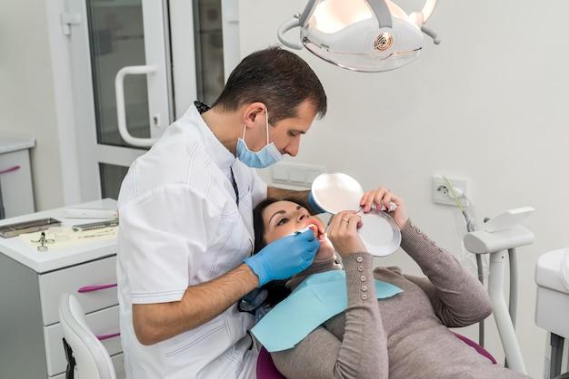 거울에 환자 치아 문제를 보여주는 의사